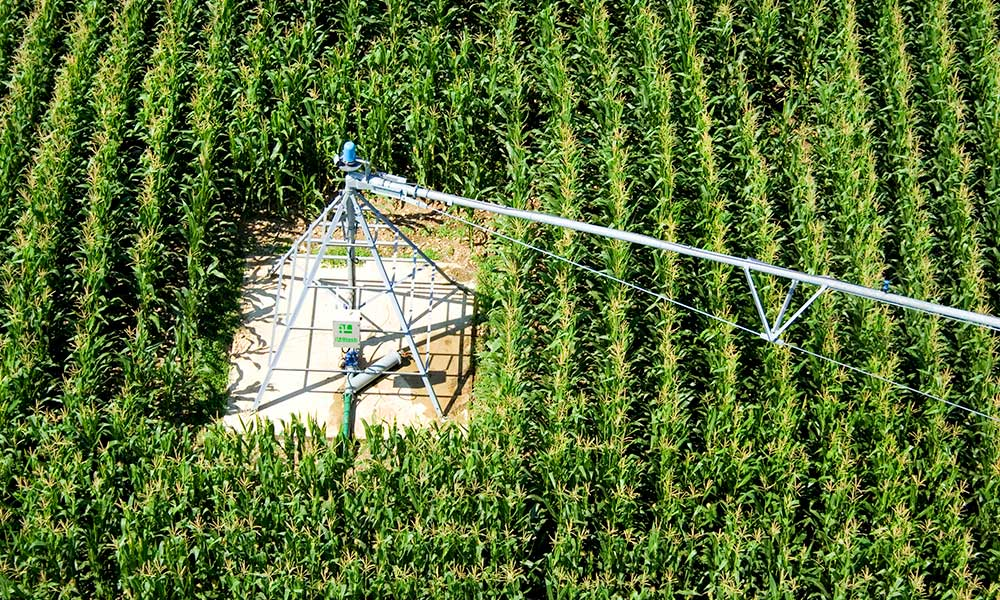 Center pivot irrigation in southwest France. The equipment rotates around a standstill center, watering crops in a surrounding circle. Photo from Wikimedia.